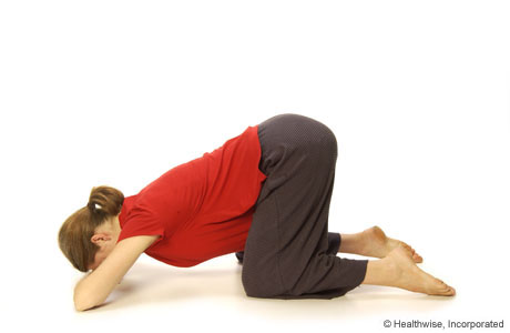 Woman leaning down with forehead on hand while on knees with feet apart