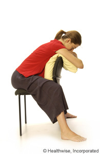 A woman sitting backwards in a chair and leaning on a pillow