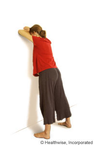 A woman leaning forward against a wall
